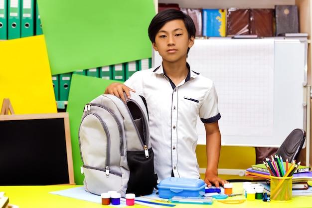 Portrait classman écolier étude assis livres asiatique garçon leçon conseil scolaire cartable sac à dos crayon globe jaune vert