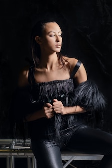 Portrait clé faible de jolie fille en veste de fourrure et pantalon en cuir sur fond sombre