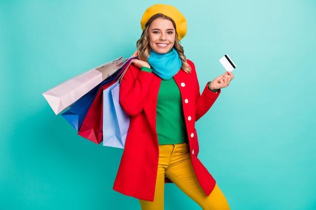 Portrait d'une cliente de magasin de fille joyeuse et positive qui aime faire du shopping avec une carte de crédit tenir de nombreux sacs porter des pantalons de chandail rouge bleu jaune vert chapeaux isolés sur fond de couleur sarcelle