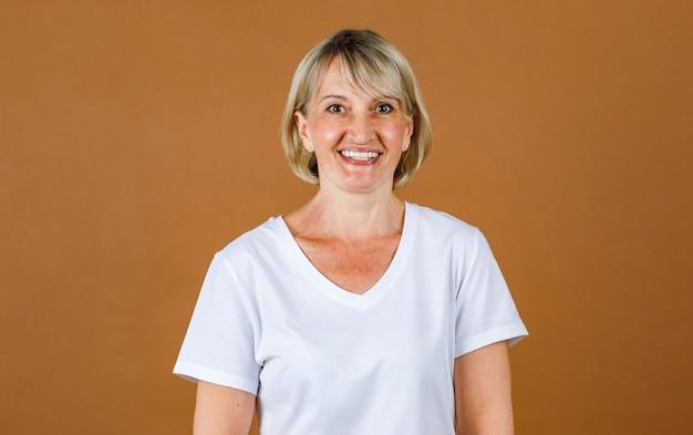 Portrait close up studio mug shot of caucasian senior heureux confiant blonde cheveux courts modèle féminin porte un t-shirt blanc propre debout souriant regarder la caméra devant un fond de papier peint marron.