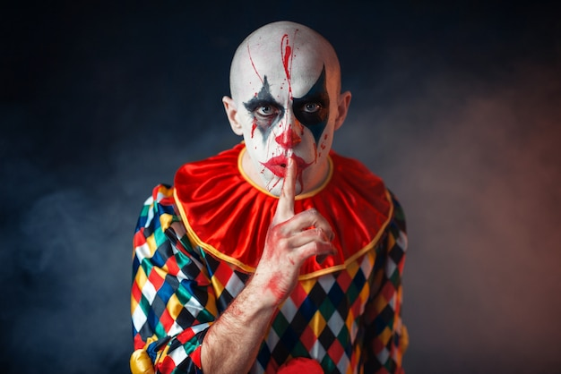Portrait de clown sanglant fou montre le signe calme