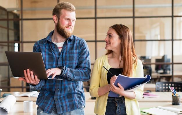 Portrait de collègues se regardant et souriant au bureau
