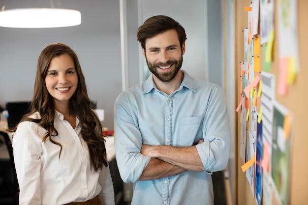 Portrait de collègues souriant debout par soft board