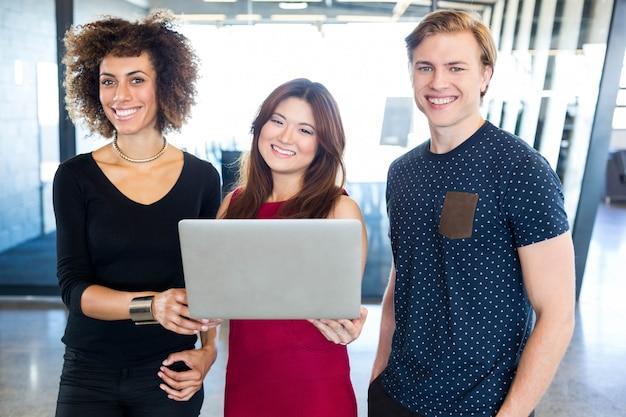 Portrait de collègues tenant un ordinateur portable et souriant au bureau
