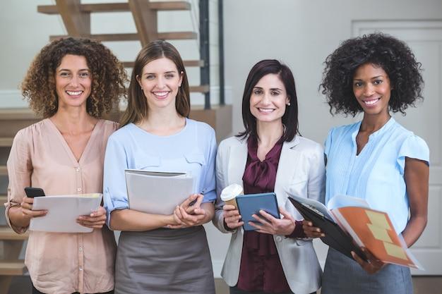 Portrait de collègues de travail féminines debout avec fichier et tablette numérique