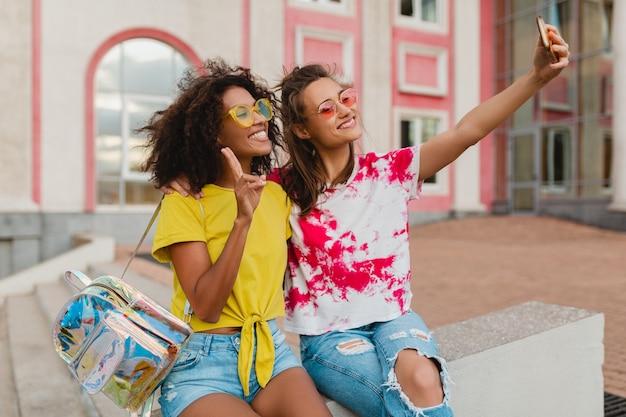 Portrait coloré d'amis heureux jeunes filles souriant assis dans la rue en prenant selfie photo sur téléphone mobile, les femmes s'amusant ensemble