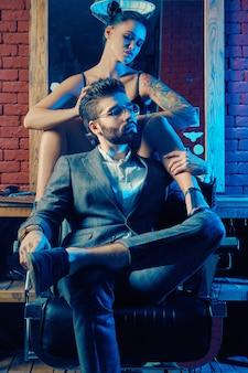 Portrait coloré de beau couple. homme en costume élégant et fille avec un tatouage portant de la lingerie en salon de coiffure