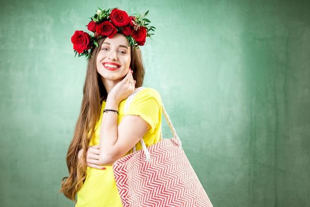 Portrait coloré d'une belle femme enceinte en t-shirt jaune avec une couronne de roses rouges tenant un sac à provisions sur fond vert