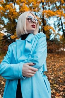 Portrait coloré élégant d'une belle femme à la mode avec des lunettes de soleil glamour dans un manteau bleu dans une forêt d'automne avec un feuillage d'automne jaune
