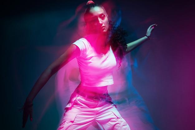 Portrait coloré de jeune fille métisse dansant en studio longue exposition néon coloré