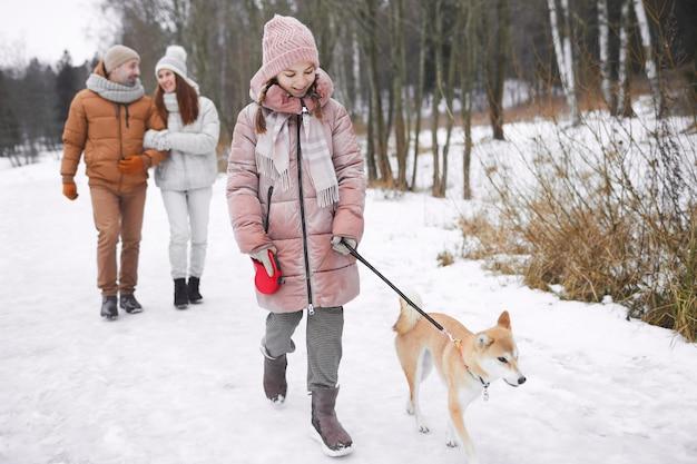 Portrait complet d'une adolescente joyeuse marchant avec un chien en laisse à l'extérieur en hiver tout en profitant de la nature en famille, espace de copie