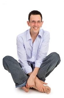Portrait complet de bel homme souriant est assis sur le flor isolé