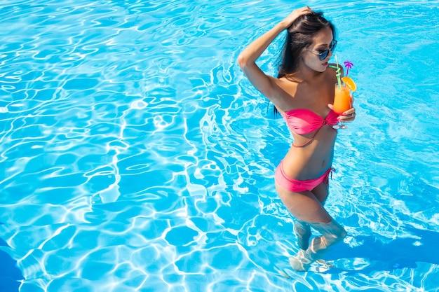 Portrait complet d'une belle femme buvant un cocktail dans la piscine