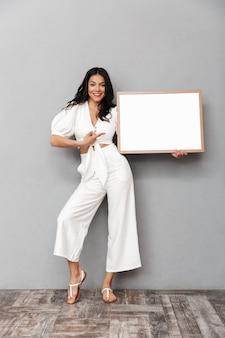 Portrait complet d'une belle jeune femme brune portant une tenue d'été isolée sur un mur gris, montrant un tableau blanc