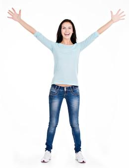 Portrait complet d'une belle jeune femme heureuse avec les mains levées, debout sur blanc