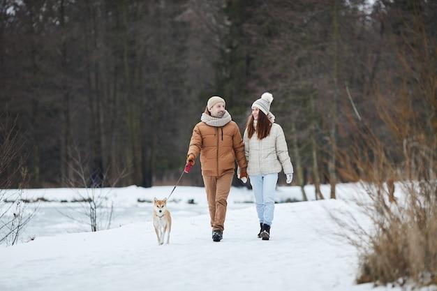 Portrait complet d'un couple adulte heureux marchant ensemble le long du lac en hiver tout en profitant de la nature avec un chien de compagnie, espace pour copie