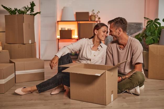Portrait complet d'un couple d'adultes heureux en train de déballer des boîtes tout en emménageant dans un nouvel espace de copie à domicile
