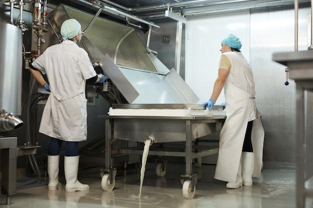 Portrait complet de deux travailleuses versant du lait caillé et égouttant le lactosérum dans un atelier à l'usine de fabrication de fromage, espace de copie