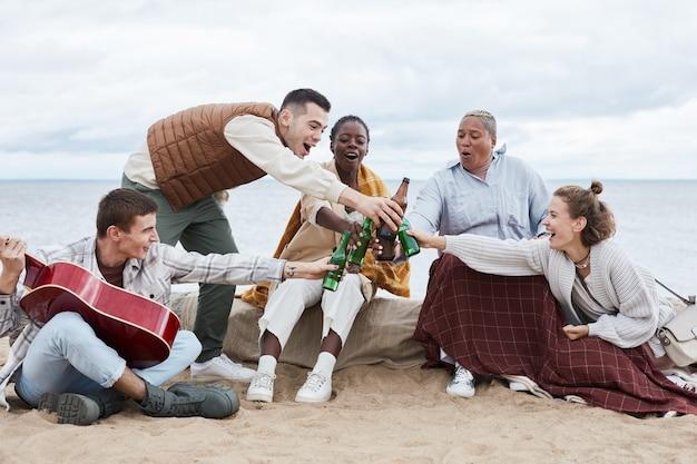 Portrait complet de divers groupes d'amis sur la plage en automne trinquant des bouteilles de bière et grillant