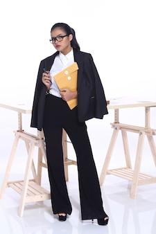 Portrait complet du corps d'une femme asiatique des années 20 portant un costume de chemise d'affaires en noir blanc. fille de peau bronzée se sentir fort confiant sur le bureau table en bois fond blanc isolé