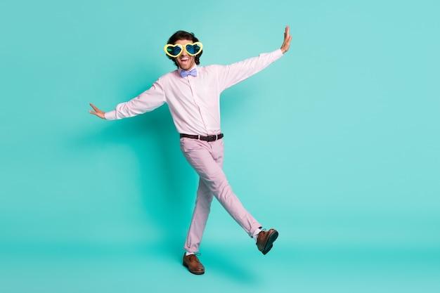 Portrait complet du corps d'un gars enfantin excité portant des lunettes d'été en forme de coeur lève la jambe isolée sur fond de couleur turquoise
