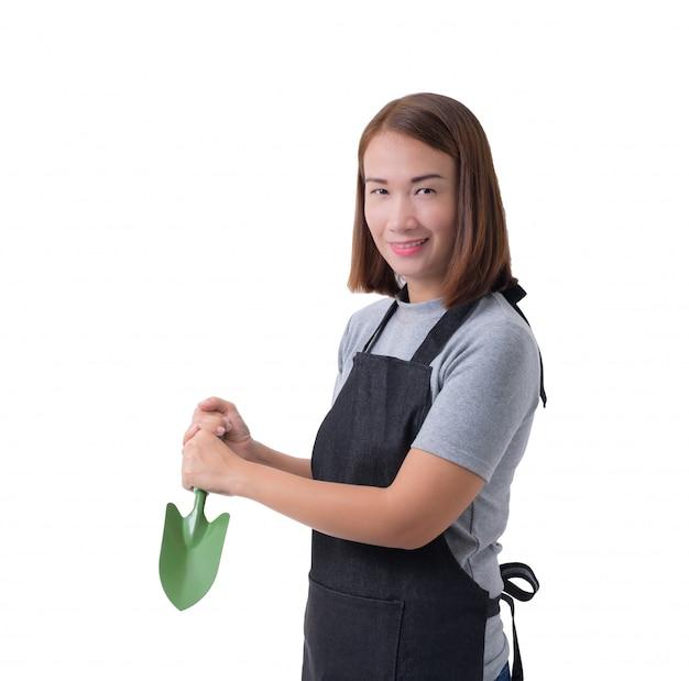 Portrait complet du corps d'une ouvrière ou d'une servante en chemise et tablier gris tient une pelle pour les cultivateurs sur fond blanc