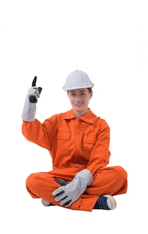 Portrait complet du corps d'une travailleuse en combinaison mécanique est assis doigt