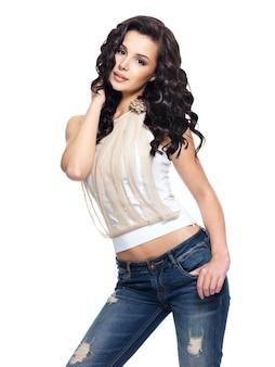 Portrait complet du mannequin aux cheveux longs vêtu d'un jean bleu