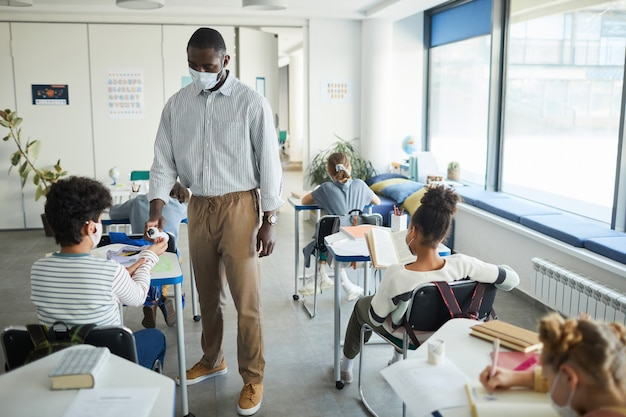 Portrait complet d'un enseignant afro-américain désinfectant les mains des enfants dans une salle de classe, espace pour copie