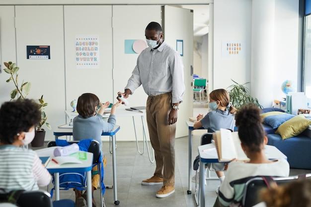 Portrait complet d'un enseignant désinfectant les mains des enfants dans la salle de classe, mesures de sécurité covid, espace de copie