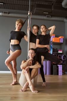 Portrait complet d'une équipe souriante de pole dance posant ensemble devant l'appareil photo dans un studio de danse