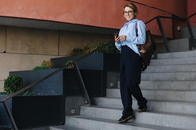 Portrait complet d'une étudiante en tenue décontractée, debout dans les escaliers et tenant un smartphone. jeune femme avec sac à dos passe du temps libre avec un gadget dans la rue.