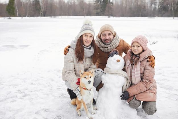 Portrait complet d'une famille heureuse construisant un bonhomme de neige ensemble à l'extérieur et regardant la caméra tout en profitant des vacances d'hiver, espace de copie