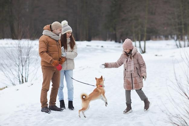 Portrait complet d'une famille heureuse jouant avec un chien à l'extérieur tout en profitant d'une promenade dans la forêt d'hiver au bord du lac, se concentrer sur une fille joyeuse portant une veste rose tenant une boule de neige, espace pour copie