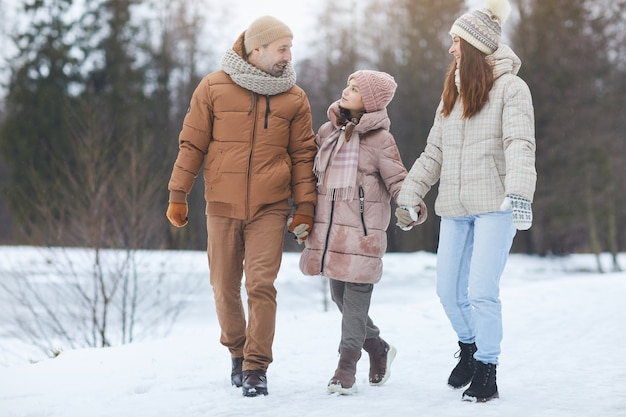 Portrait complet d'une famille heureuse moderne se tenant la main et souriant tout en profitant d'une promenade dans la belle forêt d'hiver, espace pour copie