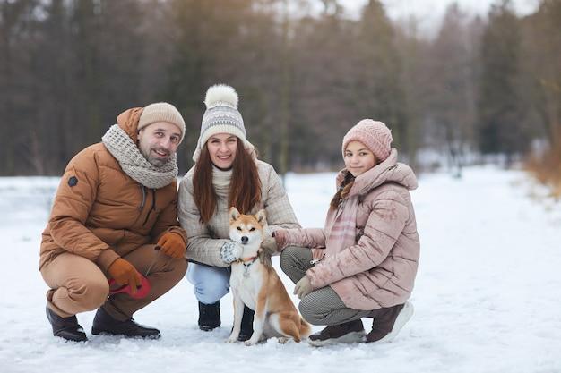 Portrait complet d'une famille heureuse regardant la caméra et souriant tout en posant avec un petit chien de compagnie lors d'une joyeuse promenade hivernale, espace pour copie