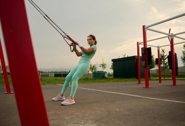 Portrait complet d'une femme afro-américaine déterminée s'entraînant avec des sangles de fitness stationnaires à l'extérieur, faisant des pompes, entraînant le haut du corps, la poitrine, les épaules, les muscles pectoraux, les triceps