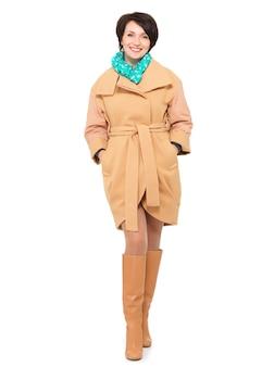 Portrait complet de femme heureuse en manteau d'automne beige et botte en cuir avec foulard vert debout isolé sur blanc