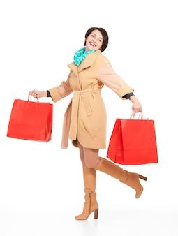 Portrait complet de femme heureuse avec des sacs à provisions en manteau d'automne avec un foulard vert debout isolé sur blanc