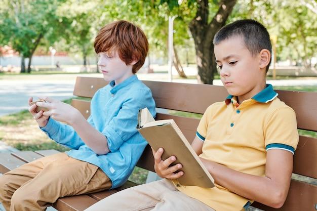 Portrait complet de garçons souriants assis sur un banc à l'extérieur avec un enseignant donnant une leçon