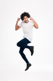 Portrait complet d'un homme afro-américain joyeux sautant isolé sur un mur blanc
