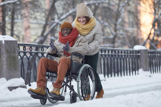 Portrait complet d'un homme afro-américain utilisant un fauteuil roulant s'amusant à l'extérieur en hiver avec une jeune femme souriante aidant, espace de copie