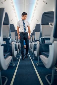 Portrait complet d'un homme confiant portant des vêtements d'affaires marchant dans l'allée d'un grand avion moderne