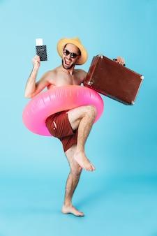 Portrait complet d'un homme torse nu joyeux portant un anneau gonflable et des lunettes de soleil, montrant un passeport, portant une valise isolée