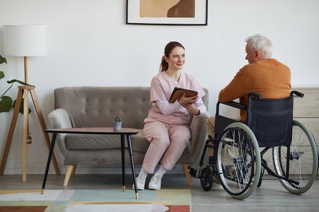 Portrait complet d'une infirmière souriante parlant à un homme âgé en fauteuil roulant et utilisant une tablette numérique à la maison de retraite, espace pour copie