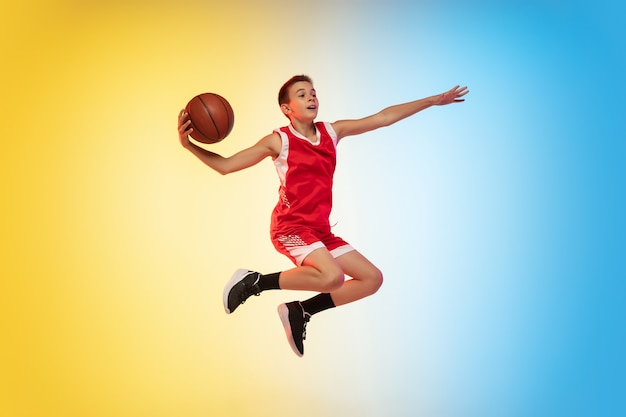 Portrait complet d'un jeune basketteur avec ballon sur mur dégradé