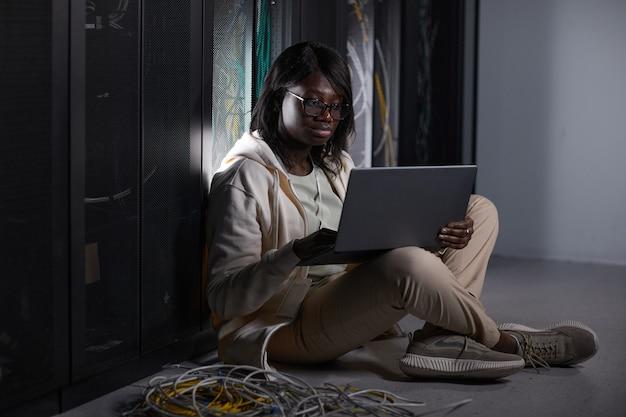 Portrait complet d'une jeune femme afro-américaine utilisant un ordinateur portable dans la salle des serveurs et assise sur le sol tout en travaillant avec un superordinateur dans un centre de données, espace de copie