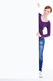 Portrait complet d'une jeune femme heureuse regarder du panneau d'affichage
