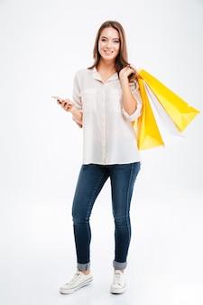 Portrait Complet D'une Jeune Femme Heureuse Tenant Des Sacs à Provisions Et Un Téléphone Portable Isolé Sur Un Mur Blanc Photo Premium