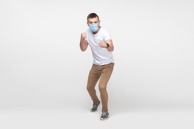 Portrait complet d'un jeune homme agressif en chemise blanche avec masque médical chirurgical debout avec des poings de boxe et prêt à attaquer ou à se défendre. tourné en studio intérieur, isolé sur fond gris.
